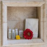 An inset, marble shelf with a towel, two flowers, and Aveda shower and soap products.