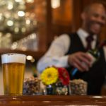 A glass of beer is on the bar with paper daisies next to it. In the background is a smiling bartender with a wine bottle in hand.