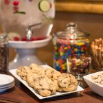 A plate of chocolate chip cookies is next to a jar of colorful chocolate candies.