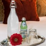 A tall bottle of still water and a small bottle of sparkling water along with two downturned glasses on a tray with a red paper daisy.